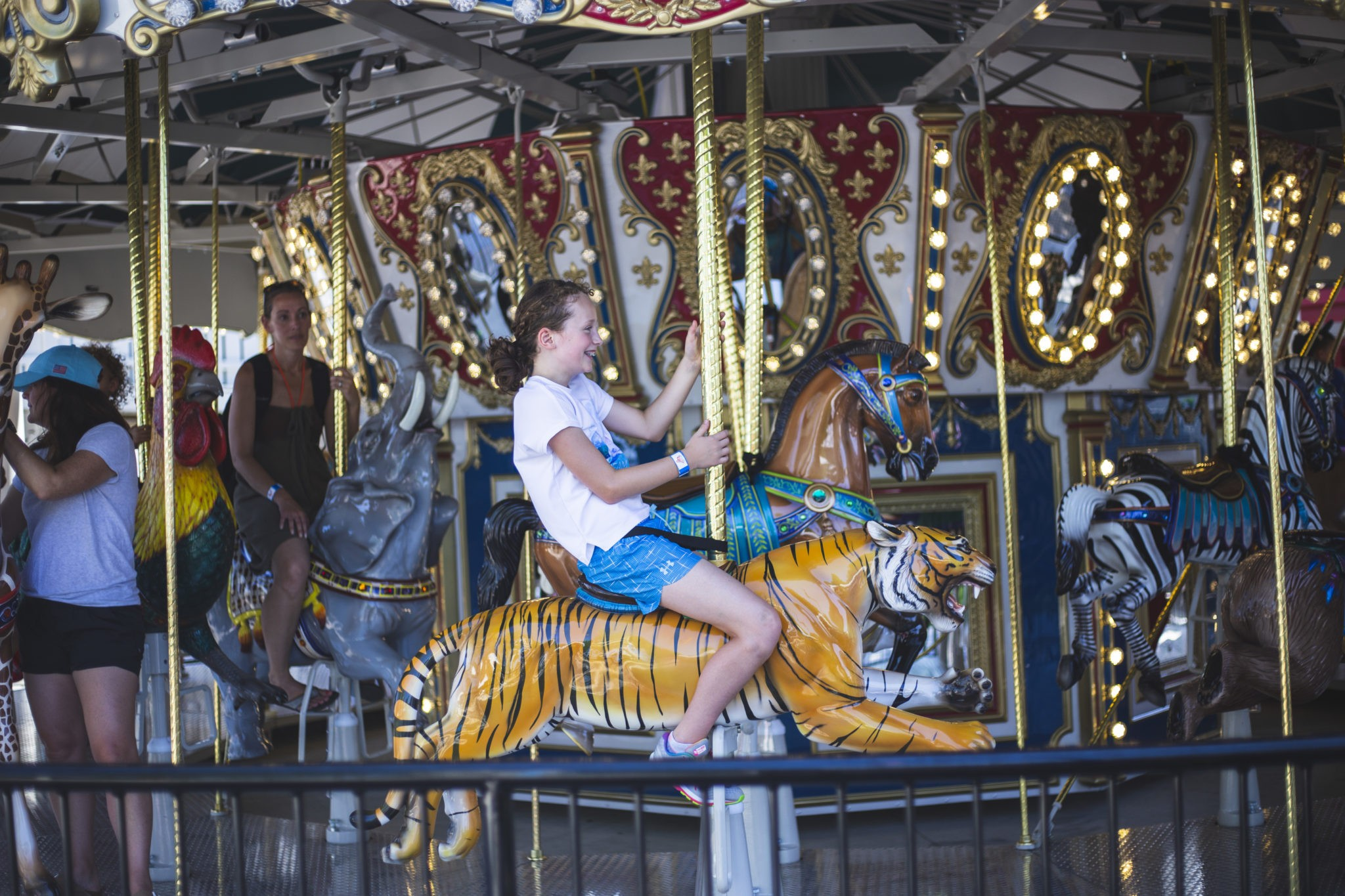 A young girl riding a tiger on the carousel.